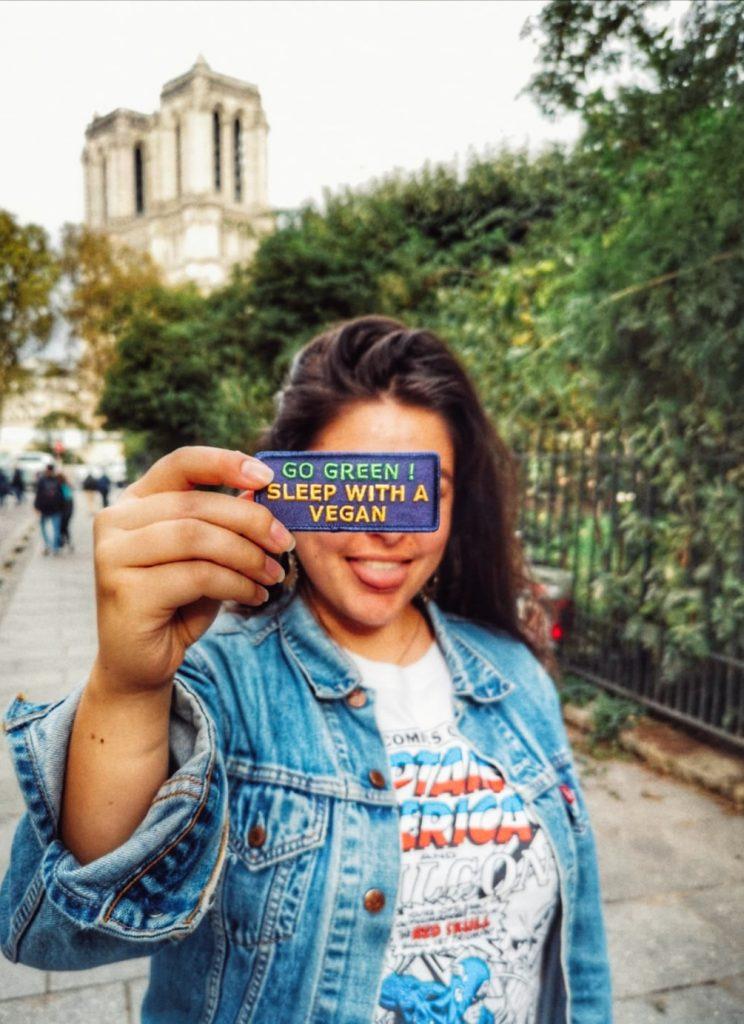 Je tire la langue avec un écusson logo végan devant Notre Dâme, à Paris.